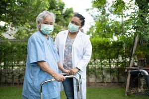 medico aiuta e cura la donna anziana asiatica usa il camminatore nel parco. foto