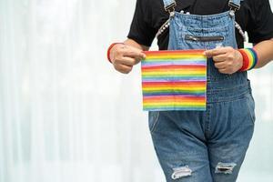 signora asiatica che tiene bandiera color arcobaleno, simbolo del mese dell'orgoglio lgbt foto