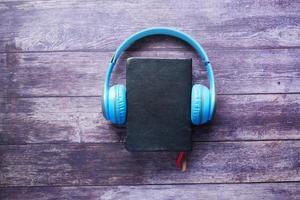 concetto di audiolibro. cuffie e blocco note su fondo in legno foto