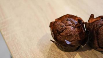 due muffin al cioccolato su un tavolo di legno foto