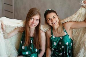 due ridenti giovani donne che si divertono quando si nascondono sotto una coperta bianca foto