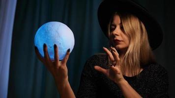 una giovane donna indovino con un cappello tiene in mano una palla magica. foto