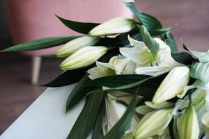 bouquet di giglio sullo sfondo di interni bianco-rosa foto