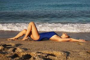 giovane donna che prende il sole in spiaggia tropicale. donna in costume da bagno blu foto