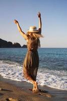 donna sulla spiaggia in un vestito marrone e con un cappello di paglia foto