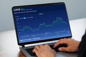 uomo che utilizza il computer che fa trading online a casa, borsa di scambio online foto