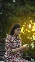 bellezza latina giovane donna in abito floreale bianco che legge sullo smartphone foto