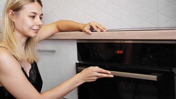 donna che cucina in cucina aprendo la porta del forno foto