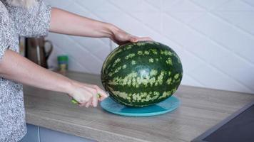 primo piano della donna che taglia a mano l'anguria in cucina foto