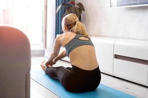 fitness donna che allunga le gambe a casa foto