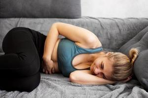 vista laterale della donna che soffre di mal di stomaco sdraiata sul divano di casa foto