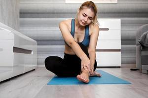 donna infelice seduta sul tappetino da yoga con infortunio alla caviglia, sentendo dolore foto