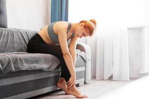 donna seduta sul divano tiene il suo piede ferito foto