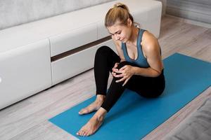 sportiva che soffre di dolore al ginocchio seduta sul pavimento foto