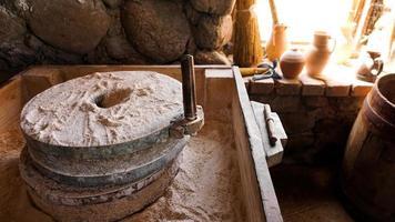 un antico mulino a mano in pietra e legno. dispositivo di macinazione della farina foto