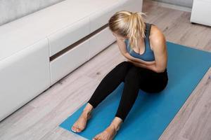 fitness donna che ha dolore allo stomaco durante l'allenamento a casa foto