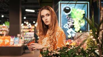 giovane donna che compra fiori in un garden center foto