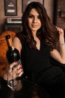 bella giovane donna sexy con i capelli lunghi che tiene in mano una bottiglia di vino foto