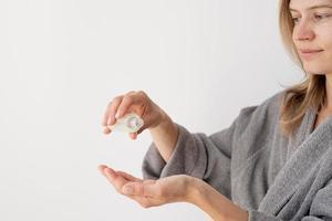 mani di donna che versano liquido dalla bottiglia foto