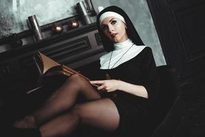 bella giovane suora in abito nero religione tiene la Bibbia. religione foto
