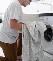giovane che mette i vestiti nella lavatrice foto