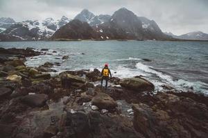 fotografo viaggiatore sulle rocce sullo sfondo del mare e della montagna foto
