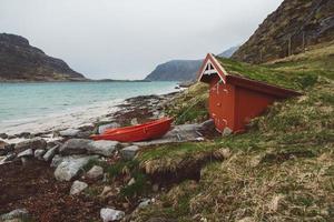 casa rossa con muschio sul tetto e barca sullo sfondo del mare e della montagna foto