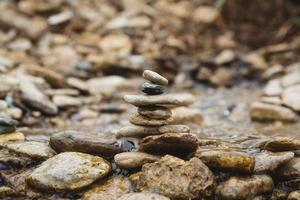 piramide di pietre sulla spiaggia di ciottoli che simboleggia la stabilità, zen foto
