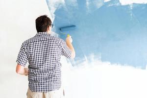 uomo che colora la parete di blu con un rullo foto