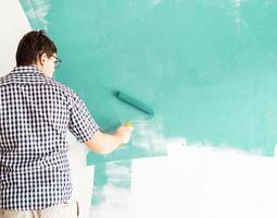 uomo che colora il muro di verde con un rullo foto