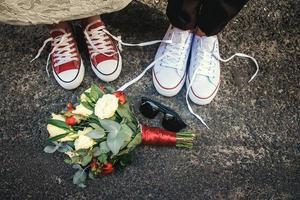 coppia di scarpe con occhiali da sole e bouquet foto