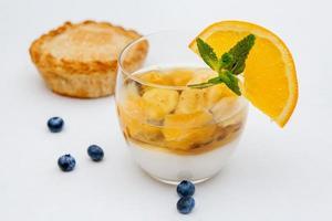 gelatina di frutta colorata in un bicchiere su sfondo bianco con mirtilli foto