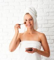 giovane bella donna che indossa asciugamani bianchi applicando uno scrub sul viso foto