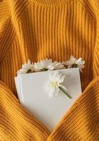 vista dall'alto di un libro con fiori di crisantemo bianco su un maglione giallo foto