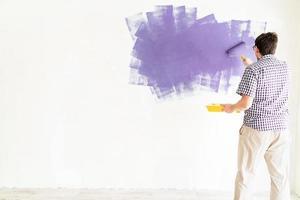 uomo che colora la parete con il rullo con vernice viola foto