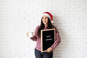 donna con cappello da babbo natale con cartellone nero foto