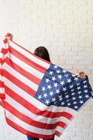 bella giovane donna con bandiera americana, vista da dietro foto