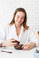 donna che indossa accappatoi facendo procedure termali utilizzando cosmetici naturali foto