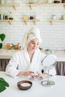 donna che applica la crema per il viso a casa foto
