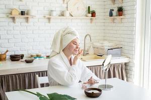 donna che si applica uno scrub per il viso sul viso foto