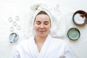 donna rilassata che ha procedure termali utilizzando cosmetici naturali foto