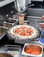 panettiere che fa la pizza nella cucina della pizzeria foto