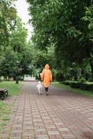 giovane donna in impermeabile arancione che cammina con il suo cane in un parco foto