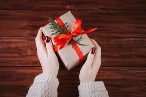 le mani tengono una bella confezione regalo su sfondo di legno. foto