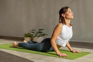 giovane donna che pratica yoga cobra posa foto