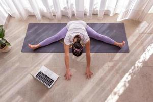 la giovane donna pratica la lezione di yoga online foto