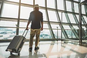 un viaggiatore maschio che indossa un cappello grigio che si prepara a viaggiare foto