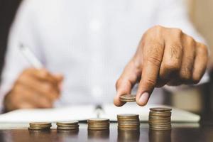 concetto bancario di risparmio delle finanze. uomo d'affari accatastamento moneta. foto