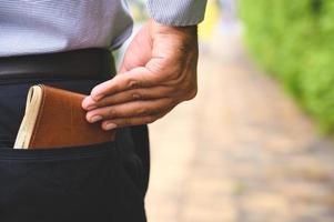 uomo d'affari che tiene al sicuro il portafoglio dei soldi nella tasca posteriore. foto