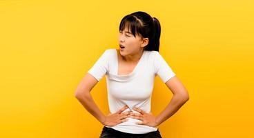 donna asiatica con forte mal di stomaco da sola su un giallo foto